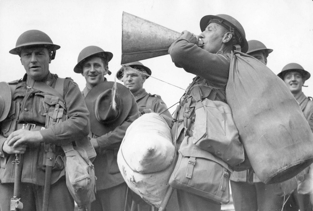 Image depicts service men in uniform one of them holds a speaking trumpet.